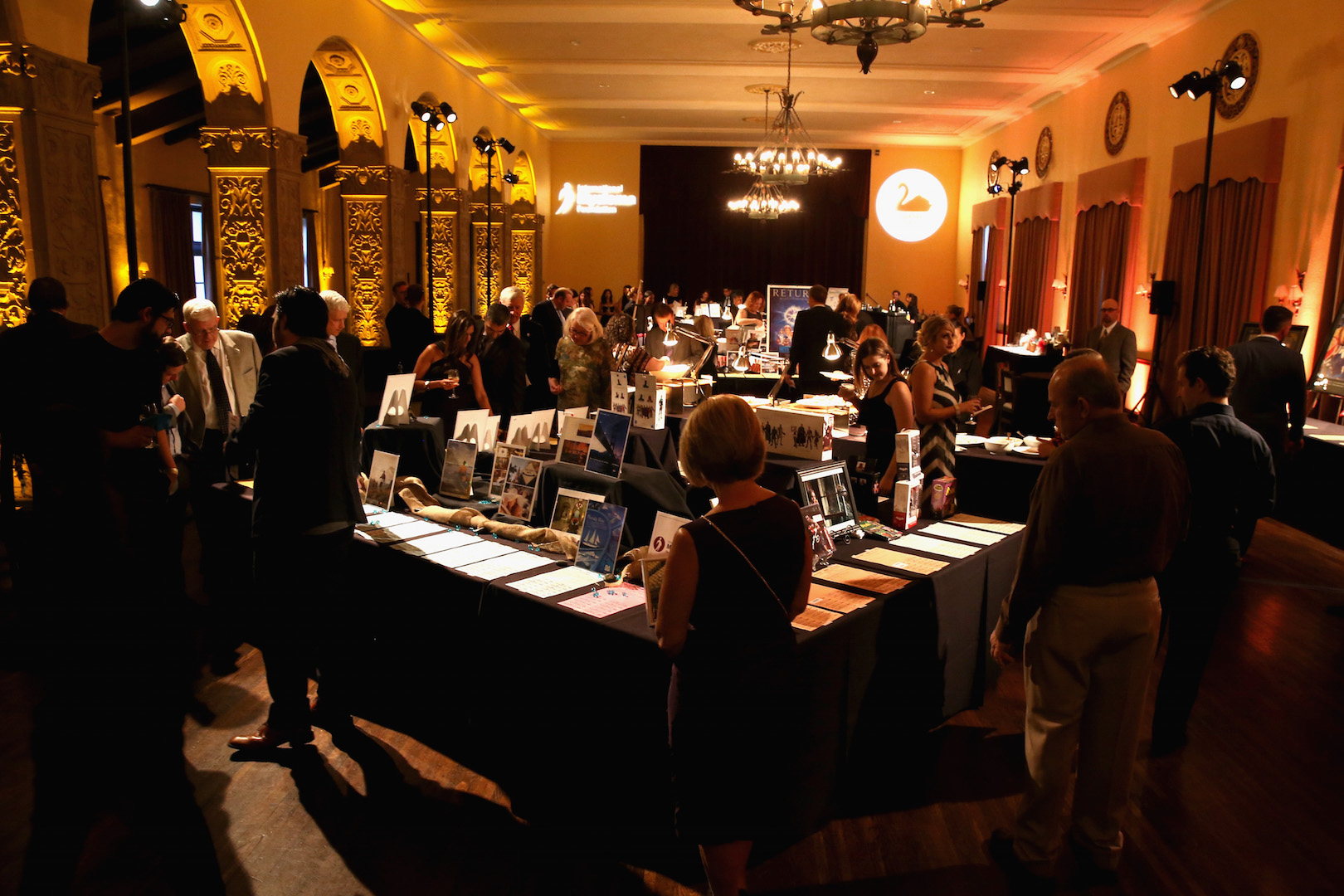 LOS ANGELES, CA - OCTOBER 10:  Guests peruse auction items on display during the 9th Annual Comedy Celebration, presented by the International Myeloma Foundation, at The Wilshire Ebell Theatre on October 10, 2015 in Los Angeles, California.  (Photo by Jesse Grant/Getty Images for for International Myeloma Foundation)