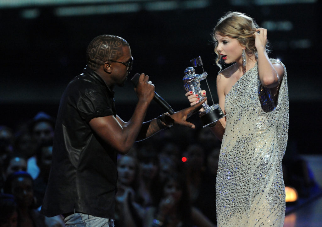 """NEW YORK - SEPTEMBER 13: Kayne West (L) jumps onstage as Taylor Swift accepts her award for the """"Best Female Video"""" award during the 2009 MTV Video Music Awards at Radio City Music Hall on September 13, 2009 in New York City. (Photo by Jeff Kravitz/FilmMagic)"""